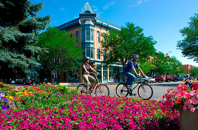 Male and female cyclists riding around Old Town Fort Collins, Colorado